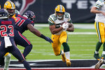 Green Bay Packers running back AJ Dillon (28) runs with the ball as Houston Texans defensive end Carlos Watkins (91) defends during the first half of an NFL football game Sunday, Oct. 25, 2020, in Houston. (AP Photo/Sam Craft)