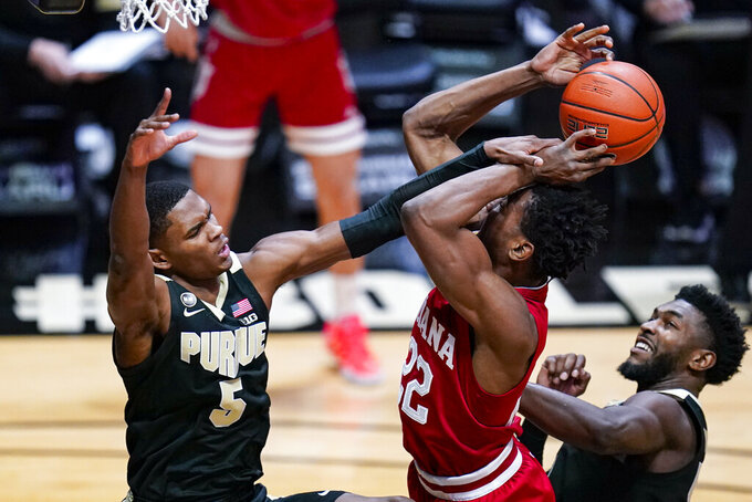Indiana forward Jordan Geronimo, center, is fouled as he shoots by Purdue guard Brandon Newman, left, during the first half of an NCAA college basketball game in West Lafayette, Ind., Saturday, March 6, 2021. (AP Photo/Michael Conroy)
