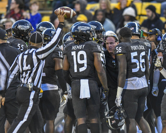 Southern Mississippi players gather around coach Jay Hopson during a timeout in the team's NCAA college football game against Western Kentucky on Saturday, Nov. 23, 2019, in Hattiesburg, Miss. (Cam Bonelli/Hattiesburg American  via AP)