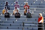 A security guard stands in front of cutouts in Alumni Stadium before an NCAA college football game between Boston College and Texas State, Saturday, Sept. 26, 2020, in Boston. The game is being played without fans present. (AP Photo/Michael Dwyer)