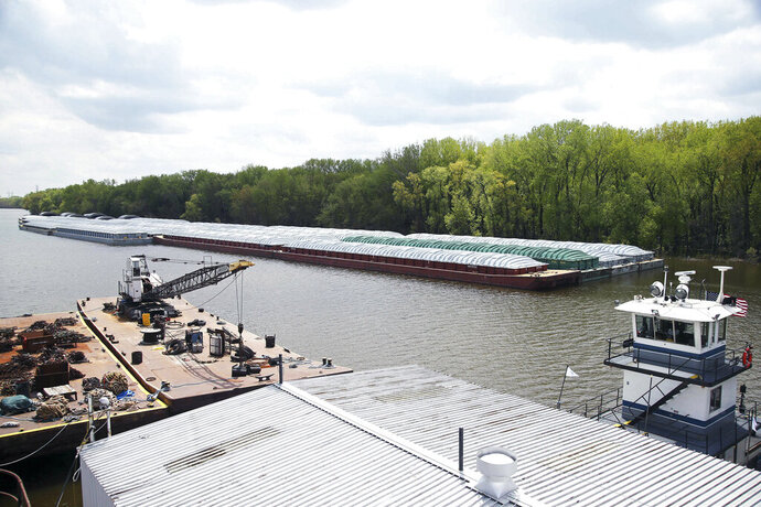 In this Tuesday, May 14, 2019 photo, barges already loaded with soy beans, potash or scrap steel await movement on the Mississippi River in St. Paul, Minn., as spring flooding interrupts shipments on the river. Historic Midwest flooding that began in March has left parts of the Mississippi River closed for business. (AP Photo/Jim Mone)