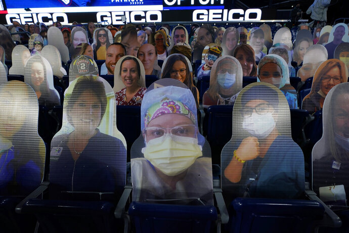 FILE - Cutout photos of people, including first responders and healthcare workers, sit in seats in Gillette Stadium before an NFL football game between the New England Patriots and the Buffalo Bills in Foxborough, Mass., in this Monday, Dec. 28, 2020, file photo. The NFL says 7,500 health care workers vaccinated for the coronavirus will be given free tickets to next month's Super Bowl to be played in Tampa, Florida. NFL Commissioner Roger Goodell also said in a news release Friday that attendance at the Feb. 7 game would be limited to those workers and about 14,500 other fans.(AP Photo/Charles Krupa, File)