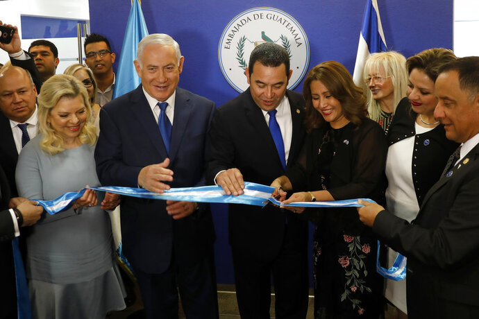Israeli Prime Minister Benjamin Netanyahu, second left, and his wife Sara, left, and Guatemalan President Jimmy Morales, center, watch as the Guatemalan First Lady Hilda Patricia Marroquin cuts the ribbon during the dedication ceremony of the embassy of Guatemala in Jerusalem, Wednesday, May 16, 2018. (Ronen Zvulun/Pool Photo via AP)