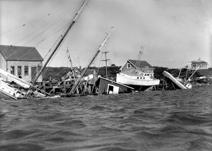 FILE - This Aug. 31, 1954 file photo shows boats driven up onto docks and buildings, and knocked into the water in the Menemsha section of Martha's Vineyard as a howling Hurricane Carol accompanied by fiercely driving rain struck New England causing millions of dollars of damage. An environmental report being released Wednesday, Aug. 4, 2021 paints a dire picture for the famous islands of Martha's Vineyard and Nantucket in Massachusetts in the face of rising sea levels and more powerful coastal storms caused by climate change. (AP Photo/DCG, File)