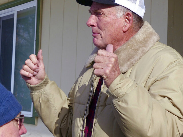 FILE - In this Jan. 2, 2016, file photo, rancher Dwight Hammond Jr. greets protesters outside his home in Burns, Ore. A judge on Friday, Dec. 20, 2019 revoked the grazing permit of two ranchers who were pardoned last year by President Donald Trump on an arson conviction for setting fire to federal lands. (Les Zaitz/The Oregonian via AP, File)