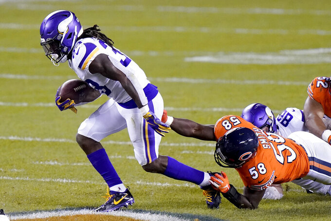 Minnesota Vikings running back Dalvin Cook, left, slips past Chicago Bears linebacker Roquan Smith (58) during the first half of an NFL football game Monday, Nov. 16, 2020, in Chicago. (AP Photo/Nam Y. Huh)