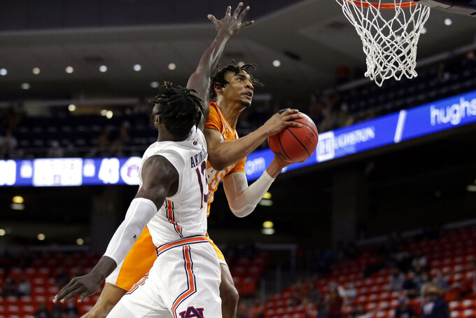 Tennessee guard Keon Johnson (45) puts up a shot around Auburn center Babatunde Akingbola (13) during the second half of an NCAA basketball game Saturday, Feb. 27, 2021, in Auburn, Ala. (AP Photo/Butch Dill)
