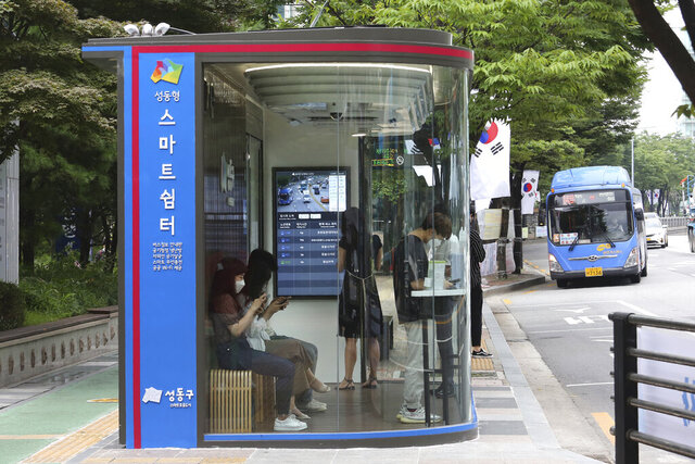 A bus shelter designed to block people with fever amid a spread of the coronavirus, is installed at a bus stop in Seoul, South Korea, Friday, Aug. 14, 2020. The glass panels-covered bus stops at a Seoul district, are equipped with thermal cameras that screen people for fevers and also automatic doors that doesn't let in any one with high temperatures. The sign reads