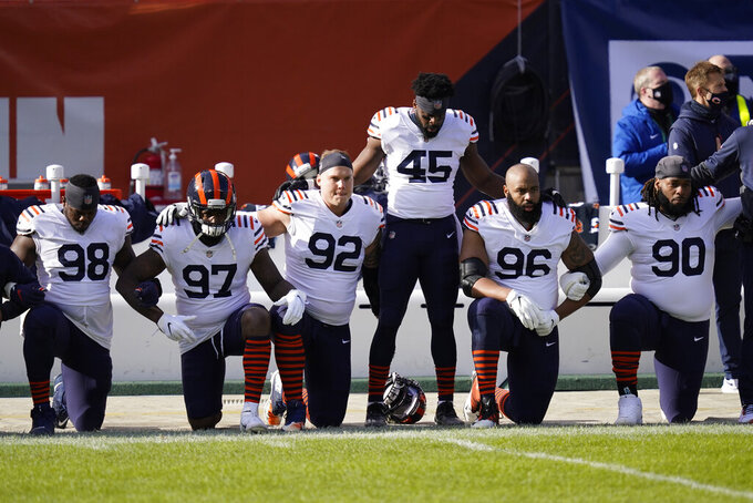 Chicago Bears players take a knee during the national anthem before an NFL football game against the Houston Texans, Sunday, Dec. 13, 2020, in Chicago. (AP Photo/Charles Rex Arbogast)