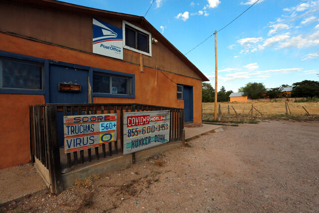 In this Sunday, Aug. 9, 2020, photo, a hand-painted sign at a post office keeps score of the COVID-19 cases and deaths in the village of Truchas, New Mexico. Nearby wilderness areas and logging roads have allowed residents to hunker down with family cookouts and outdoor recreation. (AP Photo/Cedar Attanasio)
