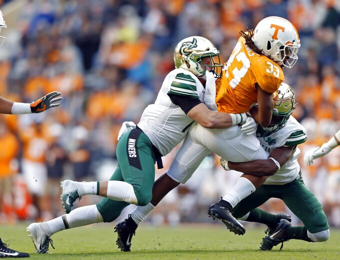 Tennessee running back Jeremy Banks (33) is tackled by Charlotte linebacker Luke Martin (17) and defensive back Ed Rolle (2) in the second half of an NCAA college football game Saturday, Nov. 3, 2018, in Knoxville, Tenn. Tennessee won 14-3. (AP Photo/Wade Payne)