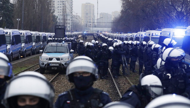 Police in riot gear block the path of anti-government protesters trying to reach the home of the ruling party leader, Jaroslaw Kaczynski, in Warsaw, Poland, Sunday Dec. 13, 2020. Thousands of anti-government protesters demonstrated in Warsaw in the latest large protest after a high court ruled in October to further tighten the country's already restrictive abortion law. Sunday's protest was scheduled to coincide with the 39th anniversary of the 1981 martial law crackdown by the country's communist regime. (AP Photo/Czarek Sokolowski)