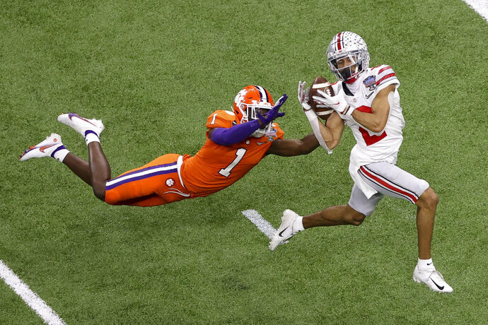 """FILE - Ohio State wide receiver Chris Olave catches a touchdown pass in front of Clemson cornerback Derion Kendrick during the second half of the Sugar Bowl NCAA college football game in New Orleans, in this Friday, Jan. 1, 2021, file photo. After the announcements of quarterback Justin Fields, cornerback Shaun Wade and other early departures trickled out via social media after the loss to Alabama in the national championship game, the Buckeyes got a huge """"stay"""" in Chris Olave, last season's leading receiver who as a junior was draft eligible. (AP Photo/Butch Dill, File)"""