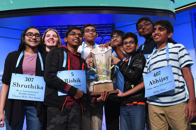 FILE - In this Friday, May 31, 2019 file photo,T he eight co-champions of the 2019 Scripps National Spelling Bee, from left, Shruthika Padhy, 13, of Cherry Hill, N.J., Erin Howard, 14, of Huntsville, Ala., Rishik Gandhasri, 13, of San Jose, Calif., Christopher Serrao, 13, of Whitehouse Station, N.J., Saketh Sundar, 13, of Clarksville, Md., Sohum Sukhatankar, 13, of Dallas, Texas, Rohan Raja, 13, of Irving, Texas, and Abhijay Kodali, 12, of Flower Mound, Texas, hold the trophy at the end of the competition in Oxon Hill, Md. The Scripps National Spelling Bee is undergoing a major overhaul to ensure it can identify a single champion, adding vocabulary questions and a lightning-round tiebreaker to this year's pandemic-altered competition, Friday, April 23, 2021. (AP Photo/Susan Walsh, File)