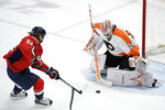 Washington Capitals left wing Carl Hagelin (62) tries to get the puck past Philadelphia Flyers goaltender Alex Lyon (34) during the second period of an NHL hockey game Saturday, May 8, 2021, in Washington. (AP Photo/Nick Wass)