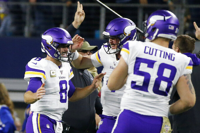 Minnesota Vikings' Kirk Cousins, Sean Mannion, center, and Austin Cutting (58) celebrate a touchdown during the second half of the team's NFL football game against the Dallas Cowboys in Arlington, Texas, Sunday, Nov. 10, 2019. (AP Photo/Ron Jenkins)
