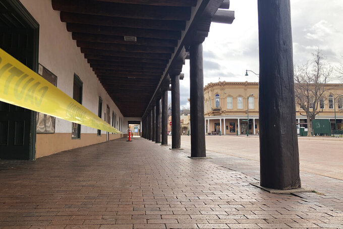 An empty central plaza and shopping district is shown amid a public health order that has closed down most retail stores and suspended dine-in restaurant service in Santa Fe, N.M., Friday, March 27, 2020. New Mexico Cabinet Secretary for Tourism Jen Schroer says the state's tourism industry will continue to suffer amid COVID-19 restrictions and vowed the state will do what it can to help hotels, tourist spots, and businesses recover once restrictions are lifted. (AP Photo/Morgan Lee)