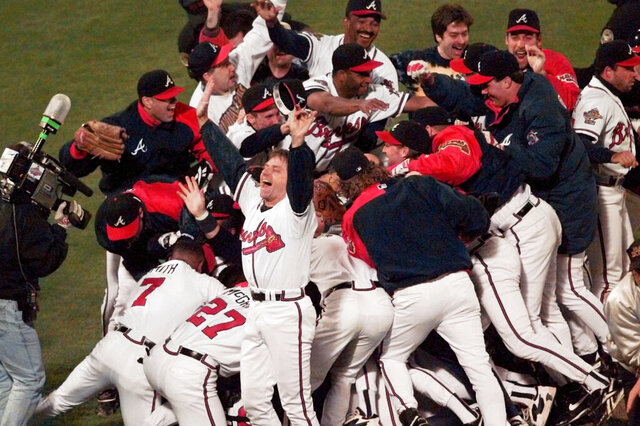 FILE - In this Oct. 28, 1995, file photo, the Atlanta Braves celebrate after Game 6 of the World Series against the Cleveland Indians in Atlanta. The Braves beat the Cleveland Indians 1-0 to win the best-of-seven series. Twenty-five years ago, Atlanta sports finally reached the promised land. With the world in the grips of coronavirus pandemic, it's a welcome respite to remember when the Braves gave the city its first major championship. (AP Photo/Ed Reinke, File)