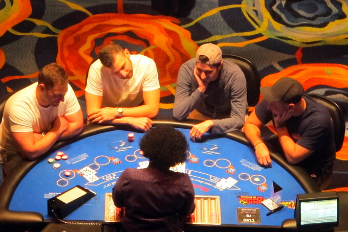 A dealer conducts a card game at the Ocean Casino Resort on Friday, June 4, 2021, in Atlantic City, N.J. Atlantic City's casinos won over $374 million in May, an increase of more than 290% from last May when they were closed due to the coronavirus, and online gambling was the only option. (AP Photo/Wayne Parry)