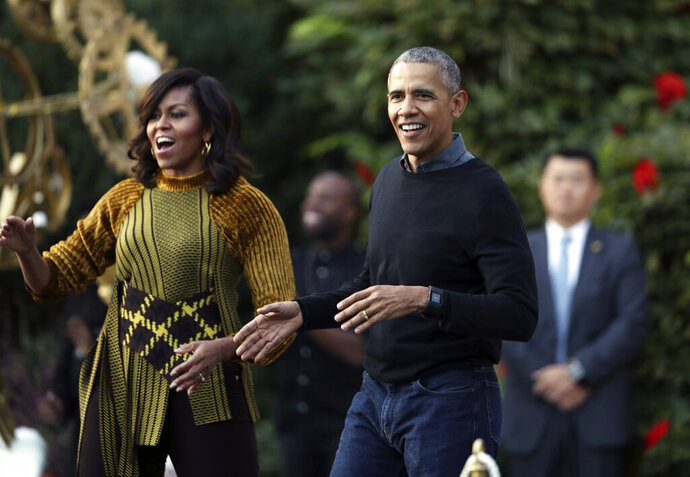 FILE - In this Oct. 31, 2016 file photo, President Barack Obama and the first lady Michelle Obama dance with kids to the beat of