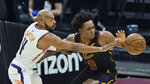 Phoenix Suns' Jevon Carter, left, fouls Cleveland Cavaliers' Collin Sexton in the first half of an NBA basketball game, Tuesday, May 4, 2021, in Cleveland. (AP Photo/Tony Dejak)