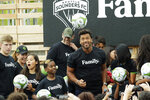 Seattle Seahawks NFL football quarterback Russell Wilson heads a soccer ball, Monday, Aug. 19, 2019, during an event in Seattle held to introduce Wilson, his wife, pop singer Ciara, hip-hop artist Macklemore, and others as new members of the Seattle Sounders MLS soccer team's ownership group. (AP Photo/Ted S. Warren)