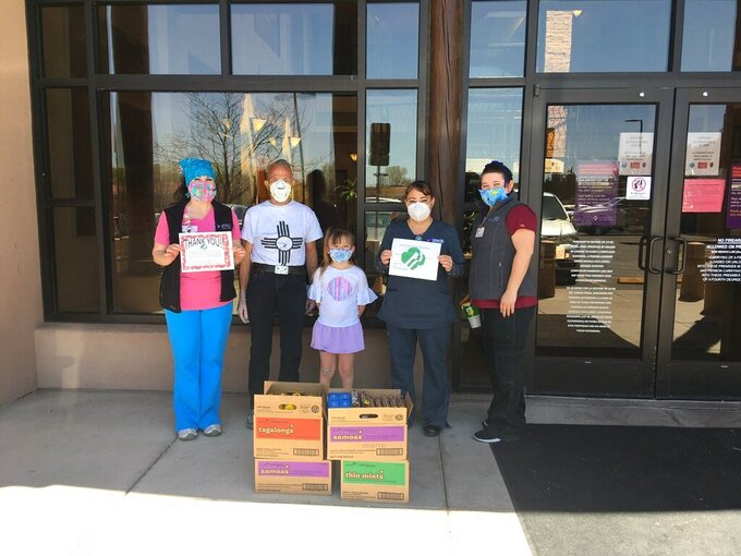 This April 30, 2020 image provided by Girl Scouts of New Mexico Trails shows health care workers with Christus St. Vincent Health System in Santa Fe, New Mexico, accepting a donation of cookies as part of the Hometown Heroes program. As the coronavirus pandemic wore into the spring selling season, many Girl Scout troops nixed their traditional cookie booths for safety reasons. That resulted in millions of boxes of unsold cookies. (Girl Scouts of New Mexico Trails via AP)