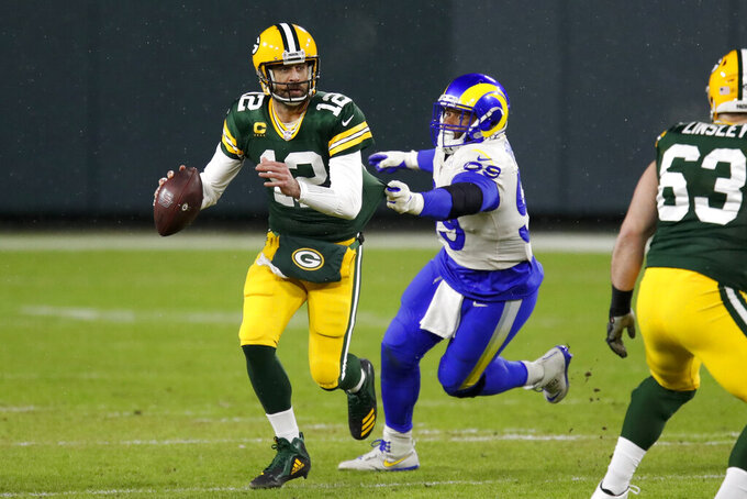 Green Bay Packers quarterback Aaron Rodgers (12) throws under pressure by Los Angeles Rams' Aaron Donald (99) during the first half of an NFL divisional playoff football game Saturday, Jan. 16, 2021, in Green Bay, Wis. (AP Photo/Matt Ludtke)