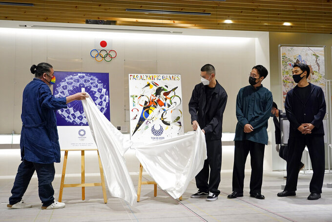 Graphic designer Asao Tokolo, left, and graphic designers group GOO CHOKI PAR members Q Asaba, third from right, Kent Iitaka, second from right, and Rei Ishii, right, unveil their posters during a presentation event in Tokyo Tuesday, June 22, 2021. The Tokyo Organising Committee of the Olympic and Paralympic Games unveiled two iconic posters hat will be used to promote the Tokyo 2020. (Franck Robichon/Pool Photo via AP)