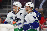 Vancouver Canucks right wing Jake Virtanen, right, celebrates his goal with Bo Horvat (53) during the third period of the team's NHL hockey game against the Detroit Red Wings, Tuesday, Oct. 22, 2019, in Detroit. (AP Photo/Paul Sancya)