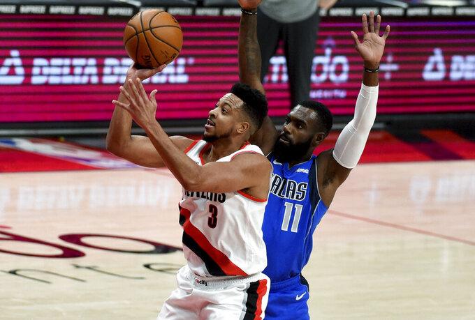 Portland Trail Blazers guard CJ McCollum, left, is fouled by Dallas Mavericks forward Tim Hardaway Jr. during the first half of an NBA basketball game in Portland, Ore., Friday, March 19, 2021. AP Photo/Steve Dykes)