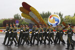 Chinese paramilitary policemen march past a decor for the Belt and Road Forum outside the special plane terminal of the Beijing International airport where foreign leaders are expected to arrive in Beijing on Wednesday, April 24, 2019. (AP Photo/Ng Han Guan, Pool)