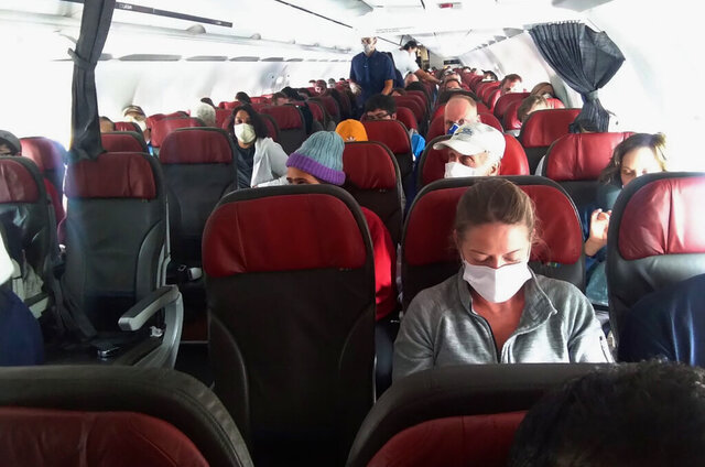 In this photo provided by a passenger who requested to be anonymous, passengers get ready before the doors close on a flight departing from Cusco, Peru, Wednesday, March 25, 2020. Anna, a 33-year-old American who had run out of life-saving medication while stranded in a Peruvian hotel room, boarded the plane home. She and her husband had been stuck as the South American nation denied landing to planes sent to bring them and others home (Courtesy photo via AP)