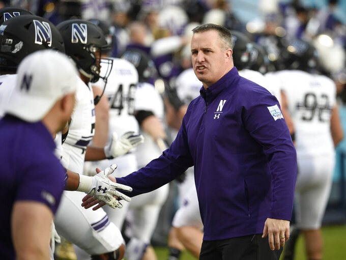 Northwestern head coach Pat Fitzgerald, right, greets players before the Holiday Bowl NCAA college football game against Utah, Monday, Dec. 31, 2018, in San Diego. (AP Photo/Denis Poroy)