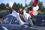 Lakeshore High School senior Isabella Najera celebrates out of her car's window during a graduation parade Sunday, May 31, 2020, at Lakeshore High School in Stevensville, Mich. School officials decided to honor the graduating seniors with the parade due to restrictions caused by the COVID-19 pandemic. (Don Campbell/The Herald-Palladium via AP)