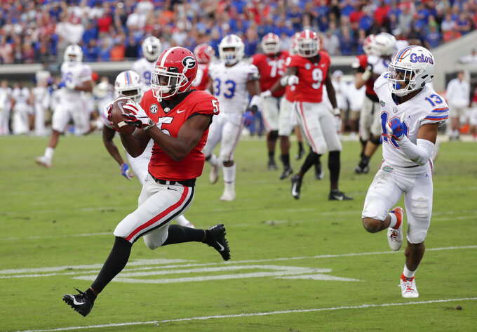 Georgia wide receiver Terry Godwin (5) catches a 24-yard pass for a touchdown as he gets past Florida safety Donovan Stiner (13) during the second half of an NCAA college football game Saturday, Oct. 27, 2018, in Jacksonville, Fla. (AP Photo/John Raoux)