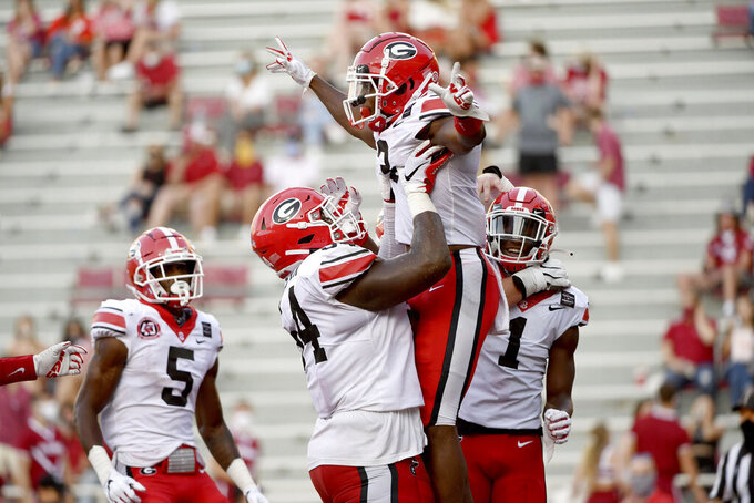 Georgia running back Zamir White (3) is lifted by Justin Shaffer (54) while celebrating his touchdown against Arkansas with  George Pickens (1) and Matt Landers (5) during the second half of an NCAA college football game in Fayetteville, Ark., Saturday, Sept. 26, 2020. (AP Photo/Michael Woods)
