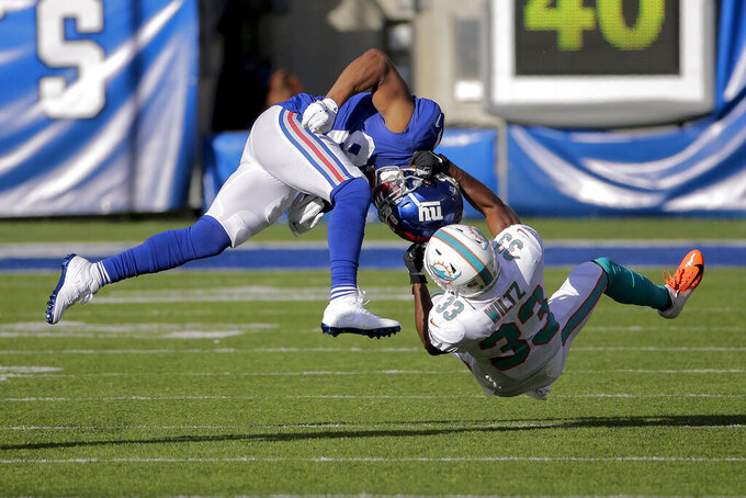 New York Giants wide receiver Sterling Shepard (87) is pulled down by Miami Dolphins cornerback Jomal Wiltz (33) during the first quarter of an NFL football game, Sunday, Dec. 15, 2019, in East Rutherford, N.J. (AP Photo/Seth Wenig)