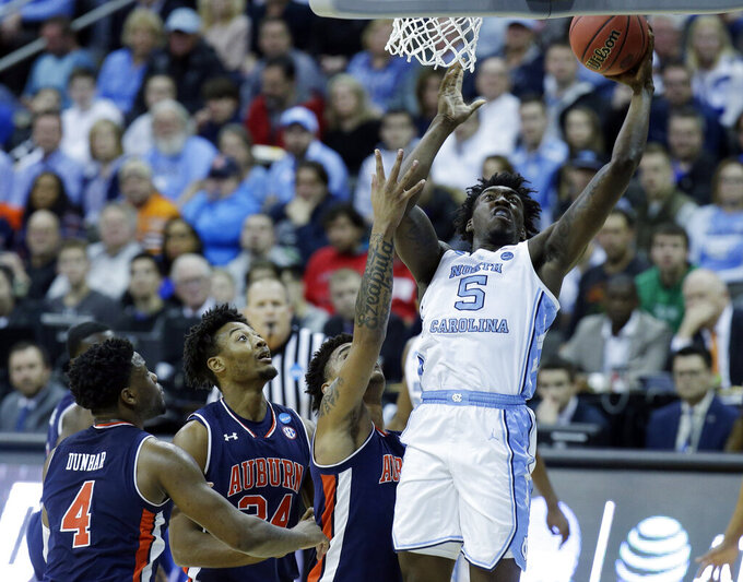 North Carolina's Nassir Little (5) heads to the basket as Auburn's Malik Dunbar (4) and Anfernee McLemore (24) defend during the first half of a men's NCAA tournament college basketball Midwest Regional semifinal game Friday, March 29, 2019, in Kansas City, Mo. (AP Photo/Charlie Riedel)