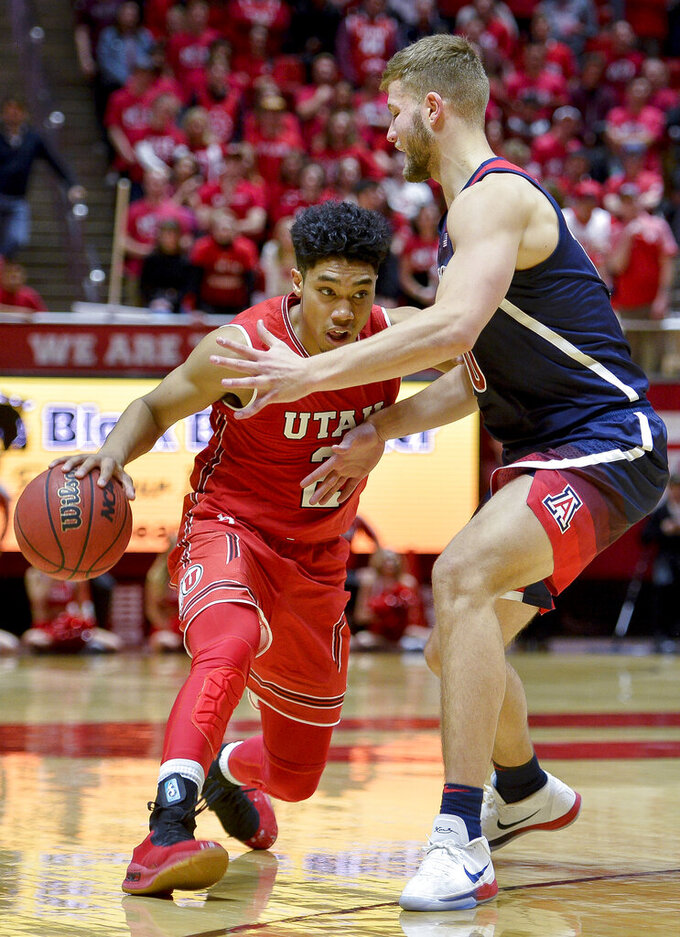 Utah guard Sedrick Barefield, left, attempts to drive past Arizona forward Ryan Luther during the second half of an NCAA college basketball game Thursday, Feb. 14, 2019, in Salt Lake City. (AP Photo/Alex Goodlett)