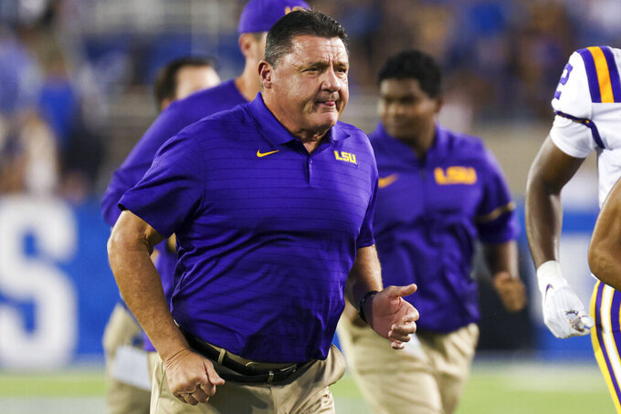 LSU coach Ed Orgeron runs off the field with his team before an NCAA college football game against Kentucky in Lexington, Ky., Saturday, Oct. 9, 2021. (AP Photo/Michael Clubb)