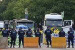 Camioneros partidarios del presidente brasileño Jair Bolsonaro protestan frente a la barrera erigida por la policía militar cuando amenazaron irrumpir en la sede de la Corte Suprema en Brasilia, 8 de setiembre de 2021. (AP Foto/Eraldo Peres)
