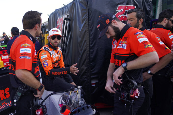 Chase Elliott talks with his crew before qualifications for the NASCAR Series auto race at Indianapolis Motor Speedway, Sunday, Aug. 15, 2021, in Indianapolis. (AP Photo/Darron Cummings)