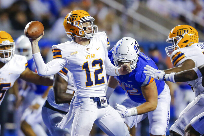 UTEP quarterback Gavin Hardison (12) looks for a receiver while coming under pressure from Boise State's Michael Callahan (92) during the first half of an NCAA college football game Friday, Sept. 10, 2021, in Boise, Idaho. (AP Photo/Steve Conner)