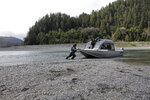 FILE - In this March 5, 2020, file photo, Hunter Maltz, a fish technician for the Yurok tribe, pushes a jet boat into the low water of the Klamath River at the confluence of the Klamath River and Blue Creek as Keith Parker, as a Yurok tribal fisheries biologist, watches near Klamath, Calif., in Humboldt County. One of the worst droughts in memory in the massive agricultural region straddling the California-Oregon border could mean steep cuts to irrigation water for hundreds of farmers this summer to sustain endangered fish species critical to local tribes. The U.S. Bureau of Reclamation, which oversees water allocations in the federally owned Klamath Project, is expected to announce this week how the season's water will be divvied up after delaying the decision a month. (AP Photo/Gillian Flaccus, File)