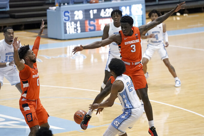 Syracuse forwards Kadary Richmond (3) and Alan Griffin (0) guard North Carolina guard Kerwin Walton (24) during the first half of an NCAA college basketball game in Chapel Hill, N.C., Tuesday, Jan. 12, 2021. (AP Photo/Gerry Broome)