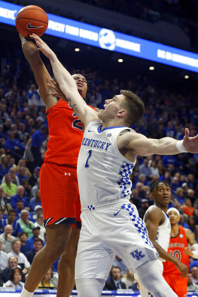Auburn's Isaac Okoro, left, shoots while defended by Kentucky's Nate Sestina (1) during the second half of an NCAA college basketball game in Lexington, Ky., Saturday, Feb. 29, 2020. (AP Photo/James Crisp)