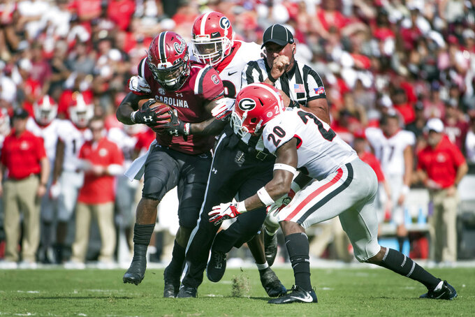 South Carolina wide receiver Deebo Samuel, left, runs with the ball against Georgia defensive back J.R. Reed (20) and Deandre Baker during the first half of an NCAA college football game Saturday, Sept. 8, 2018, in Columbia, S.C. (AP Photo/Sean Rayford)