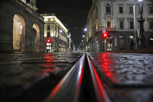 """FILE - In this Sunday, Oct. 25, 2020 file photo, an empty street in front of La Scala opera house, left, is illuminated by a red traffic light in Milan, Italy. After a rash of COVID-19 infections among musicians and chorus members, the Dec. 7 season premiere at Milan's La Scala opera house, a gala event that is one of Italy's cultural highlights, is being canceled. The theater's board of directors on Wednesday concluded that the pandemic's situation and Italy's anti-COVID-19 measures, which include closure of theaters until at least Nov. 24, won't allow for """"achieving a production open to the public and of the level and with the characteristics required""""  for the premiere. (AP Photo/Luca Bruno, File )"""