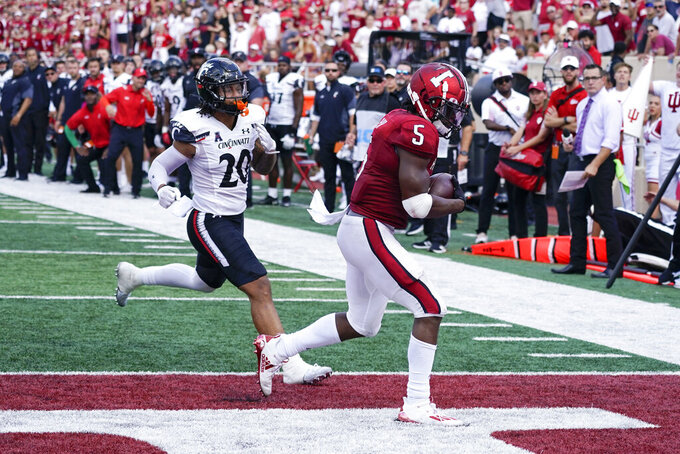 Indiana's Stephen Carr (5) makes a touchdown reception in front of Cincinnati's Deshawn Pace (20) during the first half of an NCAA college football game, Saturday, Sept. 18, 2021, in Bloomington, Ind. (AP Photo/Darron Cummings)